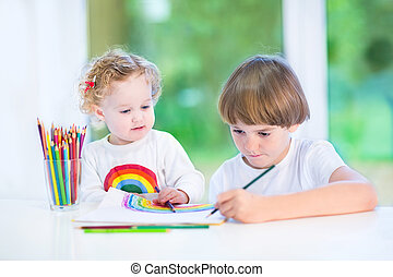 Little toddler girl watching her brother drawing with colorful p