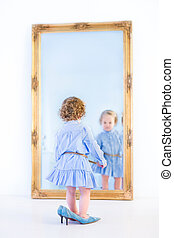 Little toddler girl with beautiful curly hair wearing a blue dre