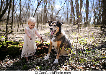Little Toddler Girl with Dirty Hands Playing in Forest with her Dog