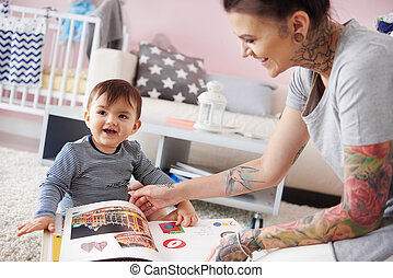 Little toddler with mum reading book