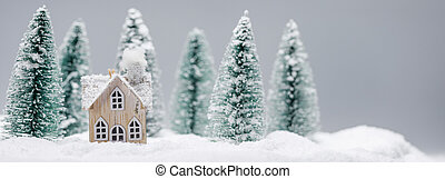 Little toy house on snow in forest