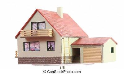 Little toy house turning around on transparent platform,...
