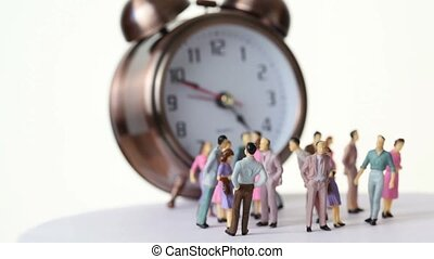 Little toy people stand in front of big clock