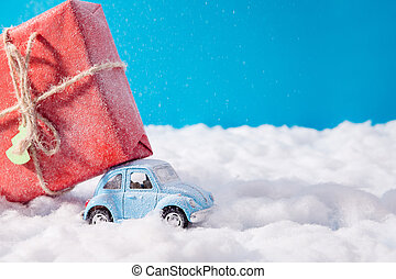 Little toy santa claus car carrying big red gift box on roof drive christmas jolly x-mas party under north-pole nature scene blue sky background