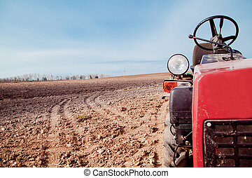 Little tractor a field in the spring