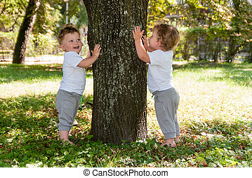 little twins, curly boys in white T-shirts, hugging a tree and smiling in the summer on the street
