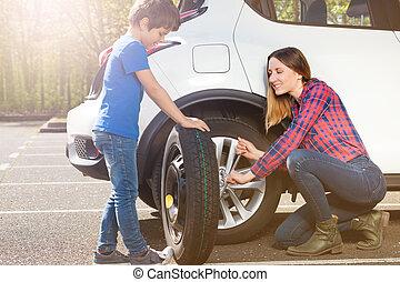 Little tyre mechanic helping mom to change a wheel - ...