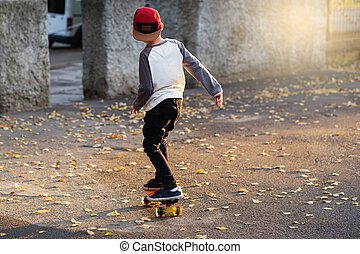 Little urban boy with a penny skateboard. Young kid riding in the park on a skateboard. City style. Urban kids.