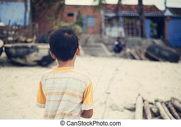 Little vietnamese boy outside his house on a beach