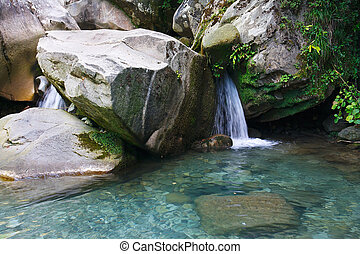 Little waterfall among the rocks in mountain forest