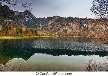 little waves with colorful nice reflection in a mountain lake while hiking