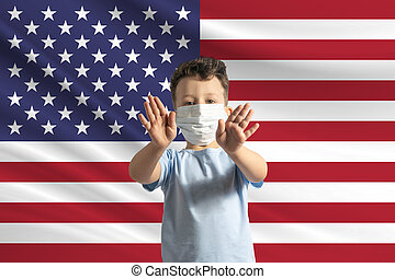 Little white boy in a protective mask on the background of the flag of United States. Makes a stop sign with his hands, stay at home United States