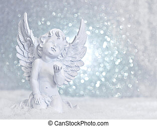 little white guardian angel in snow on shiny lights background. christmas decoration
