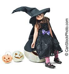 little witch sits on a pumpkin