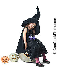 little witch sits on a pumpkin