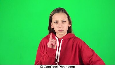 Little woman is angry and unsatisfied standing with hands at her hips on green background. Slow motion