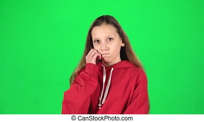 Little woman is thinking in studio on green background. Slow motion
