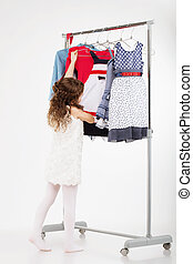 Little woman trying new clothing on white background.