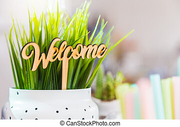 little wooden welcome sign in a white plant pot