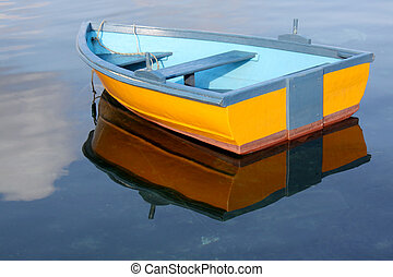 A little yellow and blue row boat floating on the water