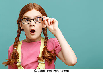 Great wonder. Close up of astonished little red-haired girl holding glasses and looking straight showing surprise.