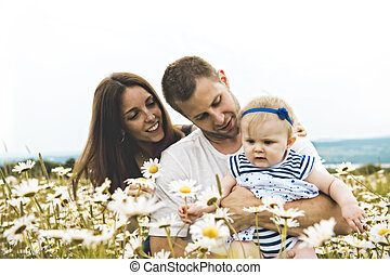 littlegirl and his father and mother enjoying outdoors in field of daisy flowers