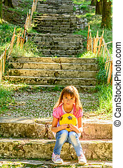 Littlle girl sitting on the stairs in the park
