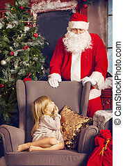 Littlle surprised girl and Santa Claus looking at her
