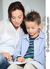 Littme boy and mother sitting on sofa at home with book