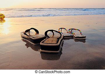 Beach sandals on the wet sandy shore