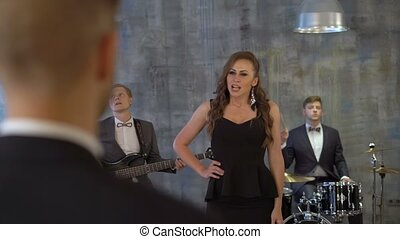 Live band with female singer perform on small private party. Beautiful sexy young woman sings song with musicians in bar, home, stage for gentleman in suit with glass of whisky