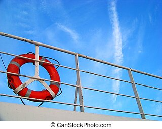 Red life buoy towards the blue sky on board of a cruise liner