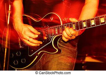 closeup of an guitarist at a rock concert, motioneffect!