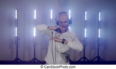 Live DJ performance of emotional energetic bald man with headphones, listening music from mobile phone. DJ composing new mix, dancing on concert musician stage. Party music festival show concert