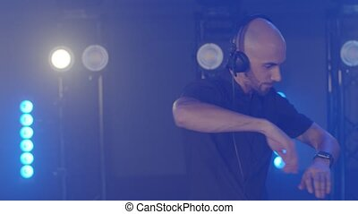 DJ composing new mix, dancing, performing on concert musician stage with lights. Party, music festival show concert. Live DJ performance of emotional energetic bald man with headphones. Slow motion