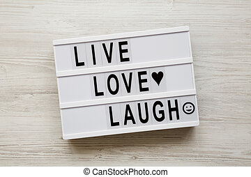 """""""Live Love Laugh' words on lightbox over white wooden background, top view. Flat lay, overhead, from above."""