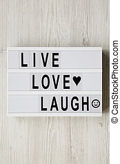 """""""Live Love Laugh' words on modern board over white wooden surface, top view. Flat lay, overhead, from above."""