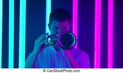 Live performance of a musician playing the trumpet. A man in a white shirt plays a jazz melody in a dark studio against the backdrop of bright neon lights. Close up. Slow motion