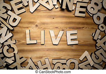 LIVE word made with block letters lying on wooden board