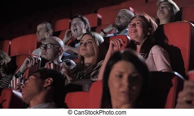 Cheerful groups, couples of audience enjoying free time in movie theater. Joyful spectators chatting, relaxing, eating popcorn, drinking soda while watching film in cinema hall