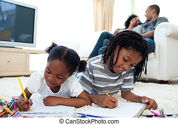 Lively children drawing lying on the floor with their...