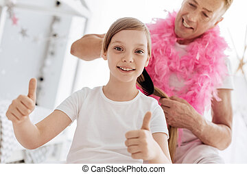 Lively enthusiastic girl getting her hair done by father