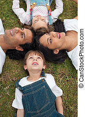 Lively family lying in a circle on the grass