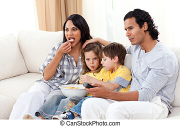 Lively family watching TV on sofa in the living room