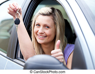 Lively female driver showing a key after bying a new car -...