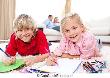 Lively siblings drawing lying on the floor in the...