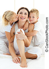 Lively siblings hugging their mother sitting on a bed