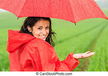 Lively teenager girl in the rain looking at camera
