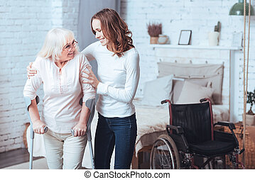 Lively young woman helping disabled aged lady at home