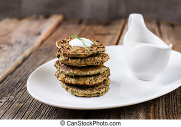 liver pancakes on a white dish with sour cream on the wooden...